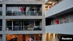 Des résidents font de l'exercice sur leur balcon à la avec des entraîneurs de fitness à Nantes, en France, pendant le confinement destiné à ralentir la propagation de la maladie à coronavirus (COVID-19) en France, le 27 mars 2020. REUTERS / Stephane Mahe