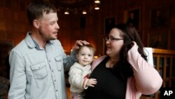 Lilly Ross holds her toddler son, Leonard, as she talks with face transplant recipient Andy Sandness, left, after their first meeting at the Mayo Clinic, Oct. 27, 2017, in Rochester, Minn.