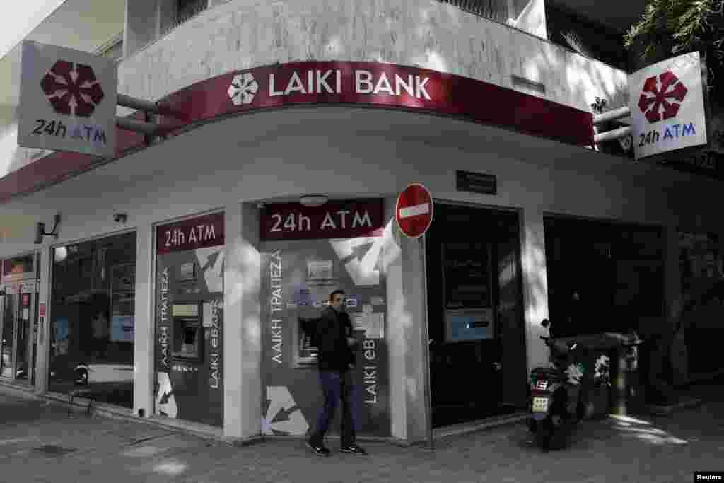 25일 키프로스 수도 니코시아 시내의 라이키 은행 자동인출기를 사용하는 시민. 키프로스는 25일 타결된 구제금융으로 부실 규모가 가장 큰 은행인 '라이키 은행'을 처분하게 되었다.