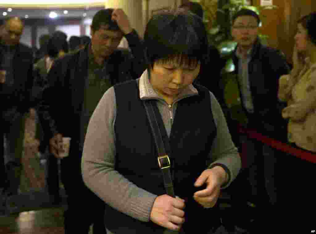Chinese relatives of passengers aboard a missing Malaysia Airlines plane walk out from a hotel room after attending a briefing by Malaysia Airlines in Beijing, March 16, 2014.