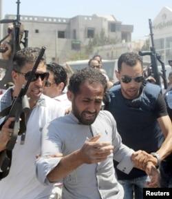 Police menangkap seorang pria (tengah) yang dicurigai terlibat dalam serangan di sebuah hotel di pinggir pantai di Sousse, Tunisia, Jumat (6/26).