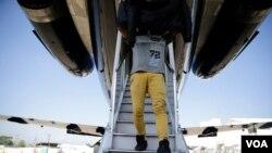 Un migrante hondureño retornado desde México desciende la escalerilla del avión que lo llevó de vuelta a su país.