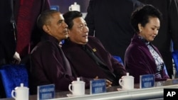 U.S. President Barack Obama, left, and Chinese President Xi Jinping, center, prepare to watch a firework show during the Asia-Pacific Economic Cooperation (APEC) summit in Beijing Monday, Nov. 10, 2014. At right is Xi's wife Peng Liyuan. (AP Photo/Wang