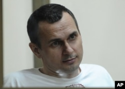 FILE - Oleg Sentsov sits behind glass in a cage at a court room in Rostov-on-Don, Russia, July 21, 2015.