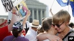 American University students Sharon Burk (L) and Molly Wagner embrace outside the Supreme Court after the court cleared the way for same-sex marriage in California by holding that defenders of California's gay marriage ban did not have the right to appeal lower court rulings striking down the ban, in Washington, D.C., June 26, 2013.