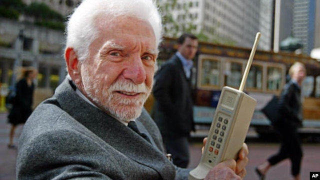 Martin Cooper, pictured here in 2003, holds the original model of the protype phone he used to make the first ever cell phone call in 1973.