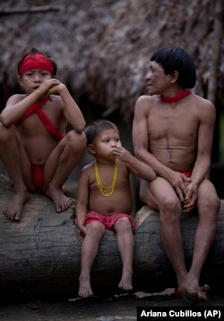 A group of Yanomami Indians sit in their village called Irotatheri in Venezuela's Amazon region, Friday, Sept. 7, 2012. (AP Photo/Ariana Cubillos)