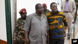 Guinea-Bissau's army chief of staff Antonio Indjai (C) and head of the national electoral commission Desejado Lima da Costa (R) arrive at a news conference at military headquarters in the capital Bissau, March 19, 2012.
