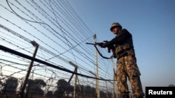 An Indian Border Security Force (BSF) soldier patrols near the fenced border with Pakistan in Suchetgarh, southwest of Jammu January 11, 2013. A flare-up in fighting on the Line of Control dividing India and Pakistan in Kashmir this week has cast a rare l