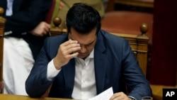 Perdana Menteri Alexis Tsipras membacakan catatannya pada pertemuan dengan parlemen di Athena, Kamis (16/7).