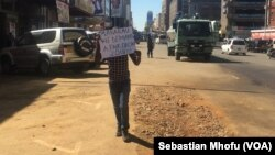"One demonstrator held a placard addressed to the electoral commission chairperson, Rita Makarau, July 12, 2017. The sign said, ""Makarau, we demand a fair election 2018!!"" Police descended on the protester and forced him into their vehicle."