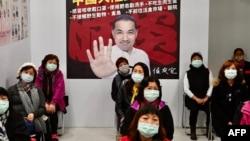 Warga berpartisipasi dalam latihan pencegahan wabah virus corona menunggu di depan poster Wali Kota New Taipei Citi Hou You-yi, di distrik Xindian, 14 Maret 2020. (Foto: AFP)