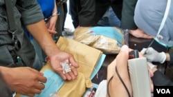 Nhân viên của Cơ quan bài trừ ma túy Indonesia xem xét các loại ma túy bị tịch thu.