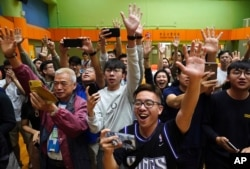 Supporters of pro-democracy candidate Angus Wong celebrate after he won in district council elections in Hong Kong, early Nov. 25, 2019.