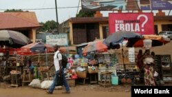 FILE – A sign urging precautions to fight the spread of Ebola hangs over a market in Guinea's capital, Conakry, Dec. 3, 2014. (Dominic Chavez/World Bank)