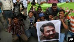 FILE - Pakistani journalists protest to condemn an attack on their colleague, Ahmed Noorani, pictured in the poster, in Karachi, Pakistan, Oct. 30, 2017.