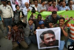 FILE - Pakistani journalists protest to condemn an attack on their colleague, Ahmed Noorani, in photo, in Karachi, Pakistan, Oct. 30, 2017.