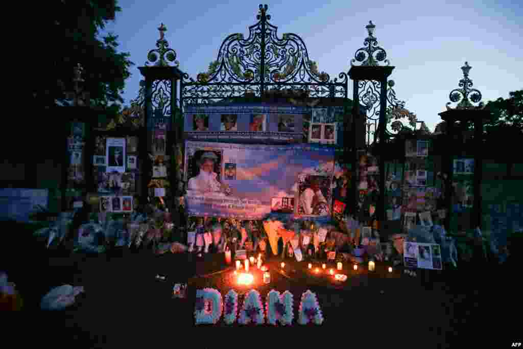 Floral tributes, candles and photographs are seen outside one of the entrances of Kensington Palace in London to mark the 20th anniversary of the death of Diana, Princess of Wales.