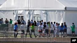 Niños inmigrantes centroamericanos hacen fila para entrar a una casa de campaña en el centro de detención temporal de Homested, Florida.