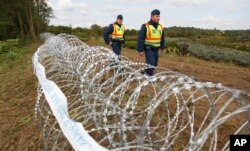 FILE - Hungarian police officers patrol an area at the temporary border fence positioned at the green border between Hungary and Croatia at Zakany, 234 km (145 miles) southwest of Budapest, Hungary, Sept. 30, 2015.