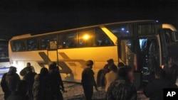 Cette photo publiée par l'agence de presse officielle syrienne SANA, montre les forces gouvernementales syriennes supervisant l'évacuation des bus des combattants rebelles et de leurs familles à Arbeen, dans la région orientale de la Ghouta, près de Damas, le 24 mars 2018.