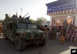 Taliban fighters stand guard at a checkpoint in Kunduz city, northern Afghanistan, Aug. 9, 2021.