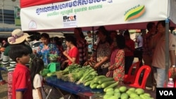 At a public market in front of the Kampong Speu market, a stall selling organic vegetables attracts dozens of passers by. (Hul Reaksmey/VOA Khmer)