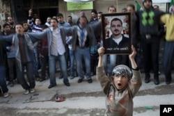Un enfant montre la photo d'un homme tué par l'armée syrienne le 24 février 2012