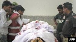 Cảnh sát, nhân viên cứu hộ và các phóng viên bên cạnh thi thể của nhà ngoại giao Ả Rập Xê-út tại nhà xác trong bệnh viện Jinnah ở Karachi, ngày 16/5/2011
