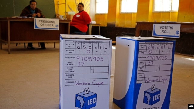 Ballot boxes await voters as Election officials (background) await their arrival after they opened early for disabled people to vote in Nyanga township before Wednesdays official elections on the outskirts of the city of  Cape Town, South Africa, May 5, 2