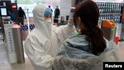 2020年1月24日農曆新年前夕,穿著防護服的工作人員檢查(到達與武漢北部接壤的)咸寧市乘客的體溫。