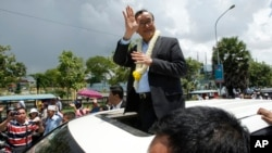 FILE - In this Aug. 16, 2015 file photo, Sam Rainsy, leader of the opposition Cambodia National Rescue Party (CNRP), waves from a car upon his arrival at Phnom Penh International Airport in Phnom Penh, Cambodia as hundreds of cheering supporters greeted him on his return from a trip abroad. The head of Cambodia's opposition party has announced his resignation from the group after the country's long-serving prime minister announced plans for a law that could lead to the party's dissolution. Rainsy announced his resignation Saturday, Feb. 11, 2017 in a letter to his Cambodia National Rescue Party.(AP Photo/Heng Sinith, File)