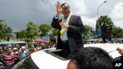 FILE - In this Aug. 16, 2015, file photo, Sam Rainsy, leader of the opposition Cambodia National Rescue Party (CNRP), waves from a car upon his arrival at Phnom Penh International Airport in Phnom Penh, Cambodia as hundreds of cheering supporters greeted him on his return from a trip abroad. The head of Cambodia's opposition party has announced his resignation from the group after the country's long-serving prime minister announced plans for a law that could lead to the party's dissolution. Rainsy announced his resignation Saturday, Feb. 11, 2017, in a letter to his Cambodia National Rescue Party.(AP Photo/Heng Sinith)