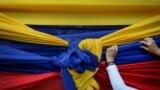 Una partidaria de la oposición sostiene una tela con los colores de la bandera venezolana antes de un mitin con el líder opositor Juan Guaidó en Caracas, Venezuela. Enero 11, 2020.
