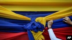 Un manifestante sostiene una tela con los colores de la bandera venezolana antes de un mitin con el líder opositor Juan Guaidó en Caracas, el 11 de enero de 2020.