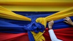 Un partidario de la oposición sostiene una tela con los colores de la bandera venezolana antes de un mitin con el líder opositor Juan Guaidó en el Montalbán de Caracas. Enero 11, 2021.