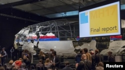 The reconstructed airplane serves as a backdrop during the presentation of the final report into the July 2014 crash of Malaysia Airlines flight MH17, in Gilze Rijen, the Netherlands, October 13, 2015.