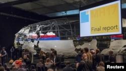 Potongan pesawat MH17 yang telah direkonstruksi sebagian, tampak di latar belakang dalam pengumuman hasil investigasi oleh para pejabat Belanda, hari Selasa (13/10).