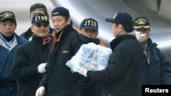 A Japanese investigator carries a battery which was taken from the All Nippon Airways' (ANA) 787 Dreamliner plane, which made an emergency landing on Wednesday, at Takamatsu airport in Takamatsu, in this photo taken by Kyodo, January 17, 2013.