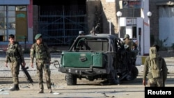 Afghan National Army (ANA) soldiers stand at the site of a blast in Jalalabad city, November 10, 2014.