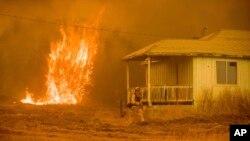 Las llamas se elevan cerca de una casa vacía cerca de Mariposa, California, el miércoles 19 de julio.
