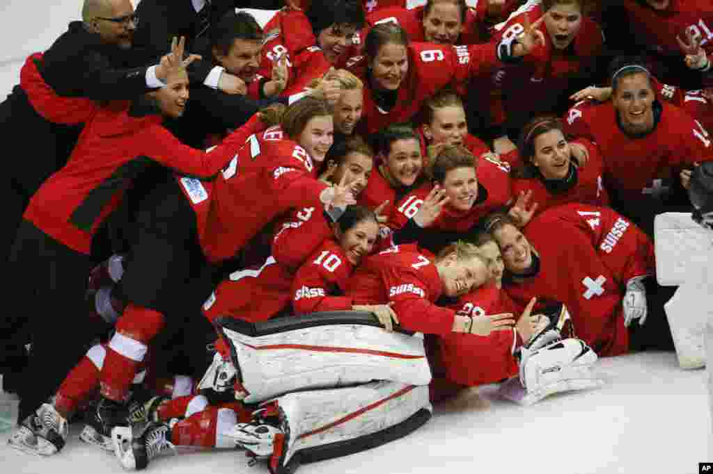 Team Switzerland poses for a picture after their 4-3 win over Sweden in the women's bronze medal ice hockey game, Sochi, Feb. 20, 2014.