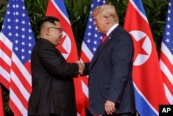 U.S. President Donald Trump shakes hands with North Korea leader Kim Jong Un at the Capella resort on Sentosa Island, June 12, 2018 in Singapore.