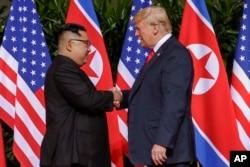 FILE - U.S. President Donald Trump shakes hands with North Korea leader Kim Jong Un at the Capella resort on Sentosa Island, Singapore, June 12, 2018.
