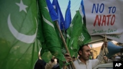 A supporter of Jamaat-e-Islami (JI), a religious and political party, holds collected party flags and placards after an anti-American demonstration in Peshawar December 2, 2011. Pakistan's commanders in the wild Afghan border region can return fire if att