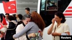 An employee (C) at Turkey's consulate in Mosul is welcomed by her relatives at Esenboga airport in Ankara, Turkey, Sept. 20, 2014.