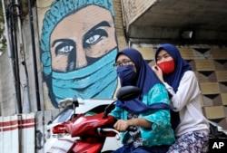Dua perempuan mengenakan masker sambil naik motor di Jakarta, Indonesia (dok: AP/Dita Alangkara)