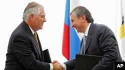 2012年6月15日,時任埃克森美孚石油公司首席執行官蒂勒森和俄羅斯石油首席執行官謝欣在俄羅斯南部黑海港口城市圖阿普謝簽約後握手。