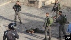 以色列警察站在一名企图刺杀耶路撒冷老城入口外的警卫时被击毙的袭击者身旁。 (2015年10月14日)