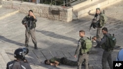 Israeli police stand around a Palestinian shot after he allegedly tried to stab a person at Damascus Gate of the Jerusalem's Old City, Oct. 14, 2015, Israeli police said.